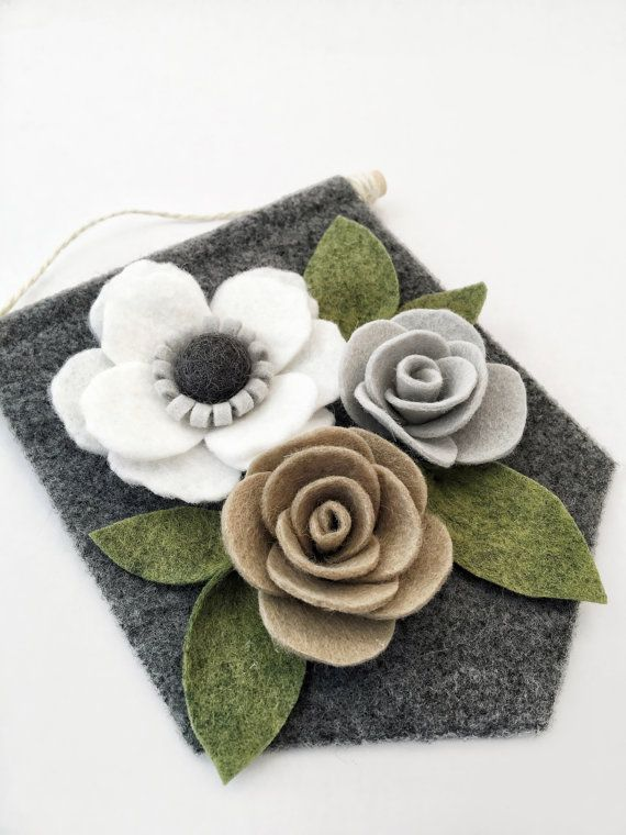 Felt Floral Banner | Made of soft and durable wool blend felt. This felt flower banner features flowers and leaves in cream, grey, taupe, green, and charcoal on a heathered charcoal felt background. The banner is made from wool blend felt wrapped around chipboard for extra stability. The back is finished with high-quality paper. Flowers and leaves are handmade and arranged on a 6 W X 6 L banner. Banner comes ready to hang from thin jute twine and has a 2 hang length. Would be the perfect…