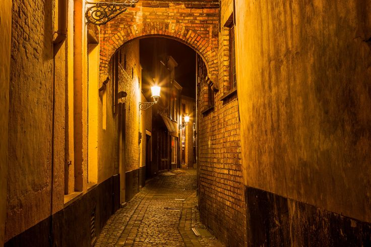 A colorfully lit alleyway, photographed at night, in the city of Bruges (i.e., Brugge), Belgium.