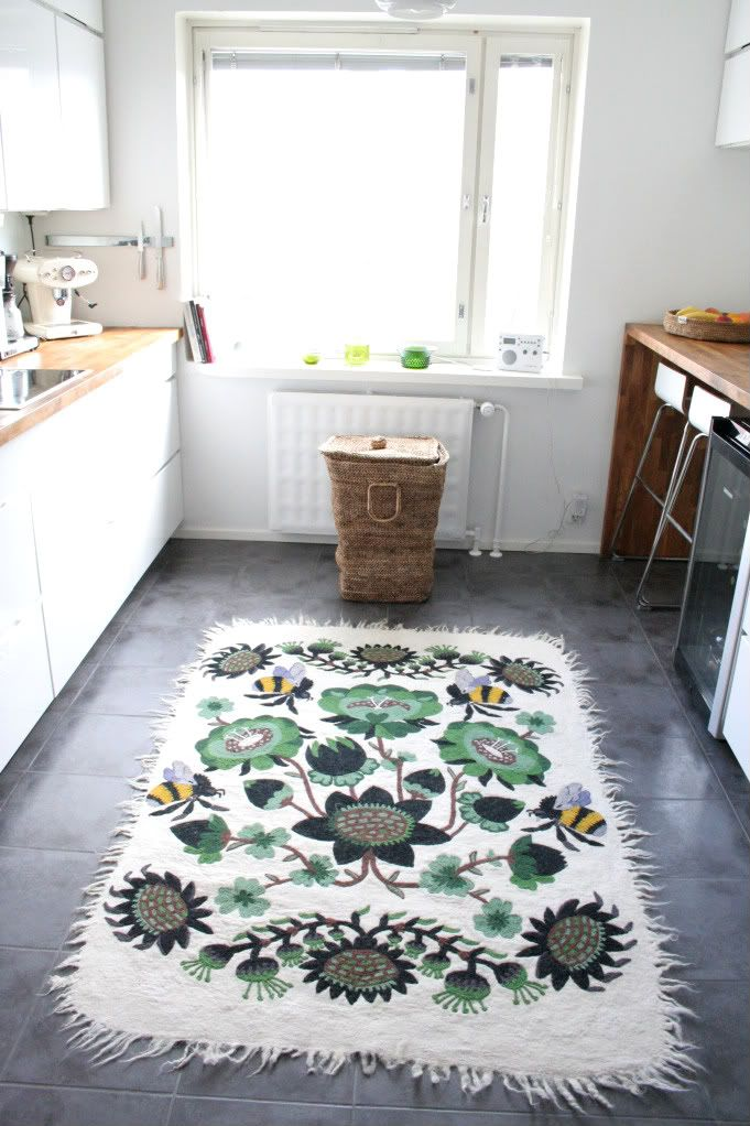 Tikau Bombroo by Klaus Haapaniemi in green colour is really warm and fresh with this white kitchen in Helsinki.