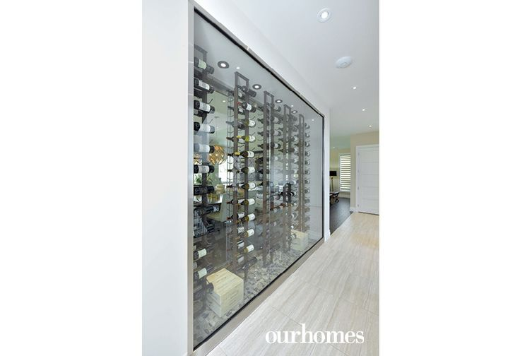 """A unique wine wall, in place of a more traditional wine cellar, was an engineering challenge overcome by a special cooling unit and UV-coated glass.    See more of this home in """"Floating Fireplace First of Its Kind in Windsor Area"""" from OUR HOMES Windsor Summer 2016  http://www.ourhomes.ca/articles/build/article/floating-fireplace-first-of-its-kind-in-windsor-area"""