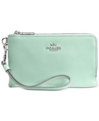 This modern update of the iconic Coach wristlet comes with two zippered compartments and a detachable wrist strap. Crafted in refined pebble leather, the design is accented with brightly polished hard