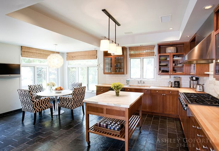 Fantastic kitchen boasts Bryant Small Billiard Light illuminating freestanding kitchen island on wheels topped with white marble across from chestnut colored cabinets paired with butcher block countertops and white subway tiled backsplash flanking stainless steel hood over integrated gas stove.