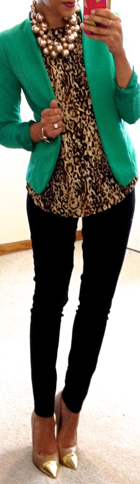 groen jasje, blouse met print en een zwarte skinny jeans.