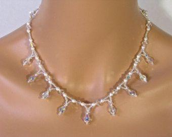 Deze Beaded Floral Lacy Bridal ketting ligt de Kate. U ontvangt de ketting en oorbellen.  Kate heeft een gelaagde look met een lichte bloemen / lacy motief. Het is drie lagen, met kleine clusters van 4mm Swarovski kristallen in duidelijke AB, 4mm Swarovski parels in wit en zaad kralen. Het heeft een solide sterling zilveren kreeft gesp. De bijpassende oorbellen hebben een solide sterling zilveren bal haak oor draden en hang ca. 1.  Deze bruids ketting zou een mooie familiestuk stuk te wo...