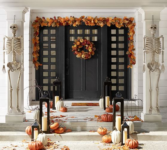 halloween decorations entry way with leaf garland skeletons pumpkins and lanterns