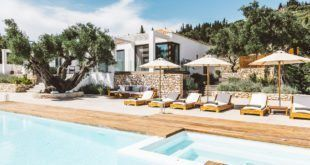 GREEK STYLE VILLAS - Sun beds with umbrellas on wooden decking by the pool.