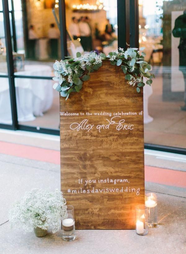 wooden wedding welcome sign with candles and baby's breath