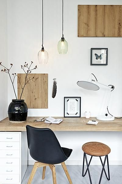black chairs, oak benchtop with white drawer unit. glass pendant lights. white lamp.