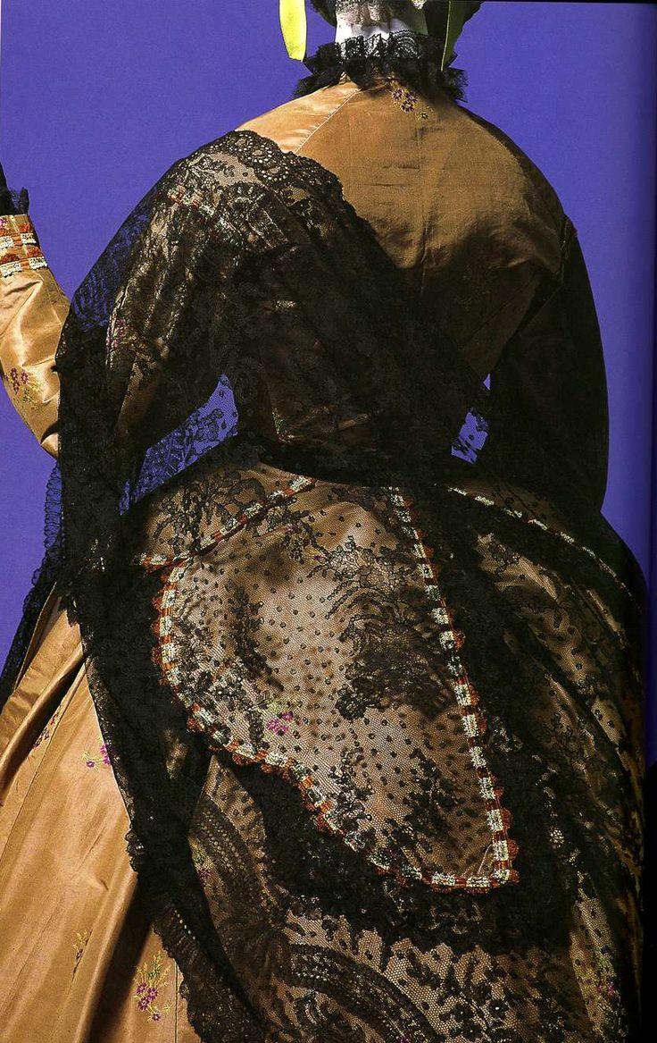 Дневное платье. Около 1865. Табачно-коричневая шелковая тафта, затканная цветочным узором, шнуры и кружева по корсажу, большая треугольная шаль из черного кружева шантильи.