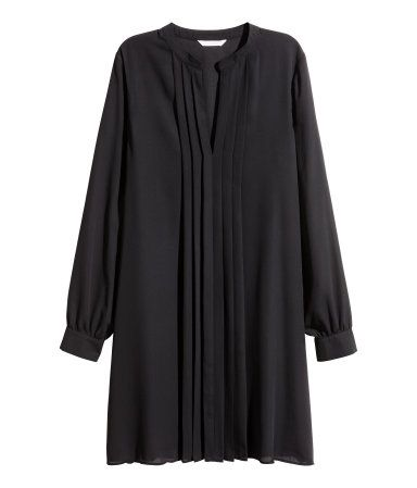 Svart. En rakt skuren klänning i crêppad, vävd kvalitet. Klänningen har låg ståkrage och är v-ringad med lagda veck fram.  Lång ärm och knäppning vid