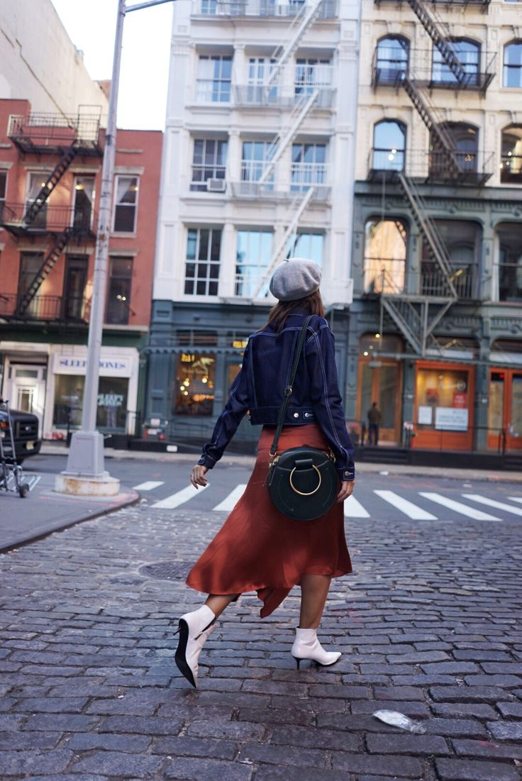street style fall / winter 2017 H&M rust satin skirt, Topshop raw denim jacket with contrast stitching, Zara white patent leather kitty heel boots, H&M grey wool beret, Zara green round crossbody bag with metal handles. Soho, New York