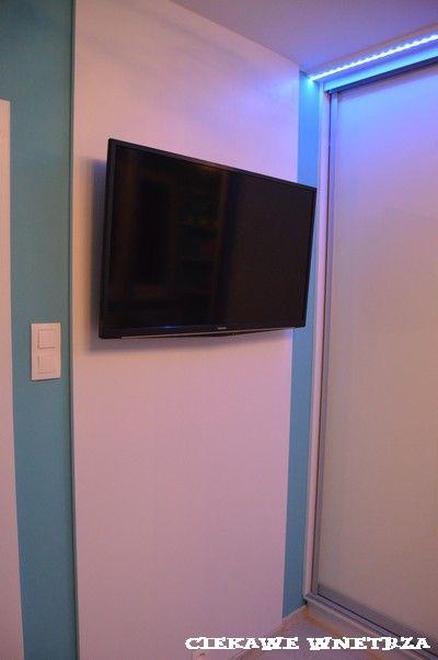 Telewizor w sypialni na panelu z białej płyty meblowej.TV in the bedroom on the panel with white chipboard.