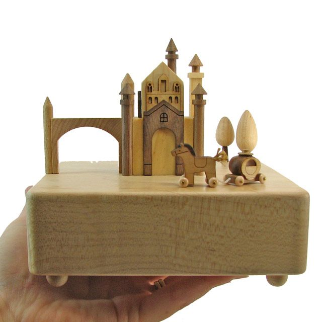 """This unique fine wood crafted music box comes with a miniature horse and carriage that circles around the castle according to variations of the theme from """"Canon in D"""". Thanks to its trademark hidden"""