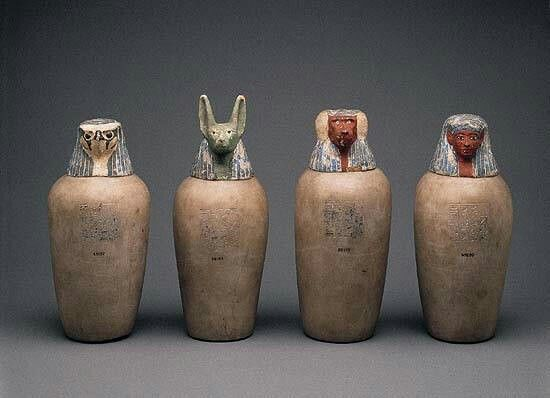 Calcite and wood canopic jars from Deir el-Bahri,Upper Egypt, 21st Dynasty c.a.1069-945 B.C. This set of jars belonged to the lady Neskhons,wife of the High Priest of Amun,Pinedjem II, and are inscribed with her name and numerous titles.The wooden lids are painted in brilliant colours and constitute one of the finesh collective images of the Sons of Horus.