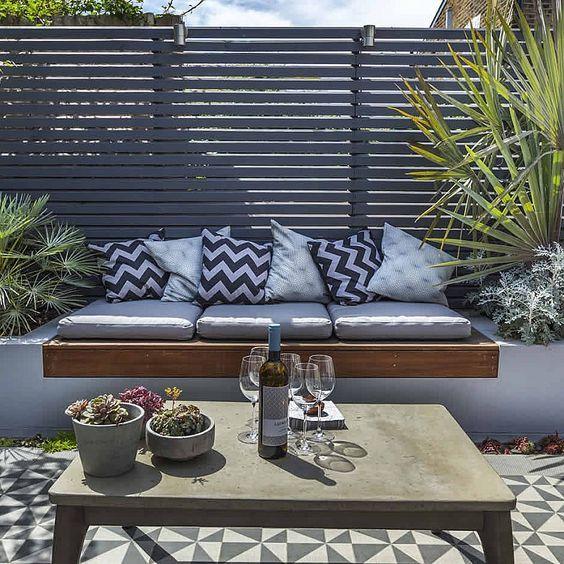 διακοσμητικα μαξιλαρια σε ένα χτιστό καναπέ δημιουργούν εντυπωσιακό αποτέλεσμα σε συνδιασμό με το πλακάκι