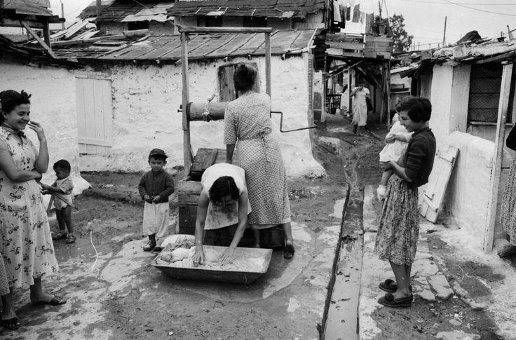 πουγάδα στο χέρι.Όλη η γειτονιά μαζί . Μανάδες και μικρά παιδιά. οι άντρες λείπουν στο μεροκάματο...Τα πιτσιρίκια έκαναν μπάνιο υπαίθρια και σε αυτό χρησίμευε η περίφημη σκάφη. Στην αρχική φωτογραφία η μεγάλη λεκάνη χρησίμευε για πλύσιμο των ρούχων στο χέρι, αλλά και για λουτρό των μικρών παιδιών που έμπαιναν μέσα και λούζονταν. Οι καλύτερες λεκάνες ήταν αλουμινιένες και φυσικά ήταν ακριβότερες.... Dourgouti-N.Kosmoq 1955 (2)