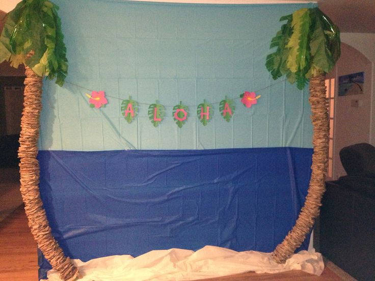"""Tropical background. Each palm tree is made with 2 pool noodles duct taped together and 80 crunched brown paper lunch bags. The palms made with two different green tissue paper and green cellophane with 2 cloth stem wires per palm. The sky ocean and sand are 3 plastic table cloths. The sign is made from the """"life is a beach"""" cricut cartridge. Total cost for background about $25"""