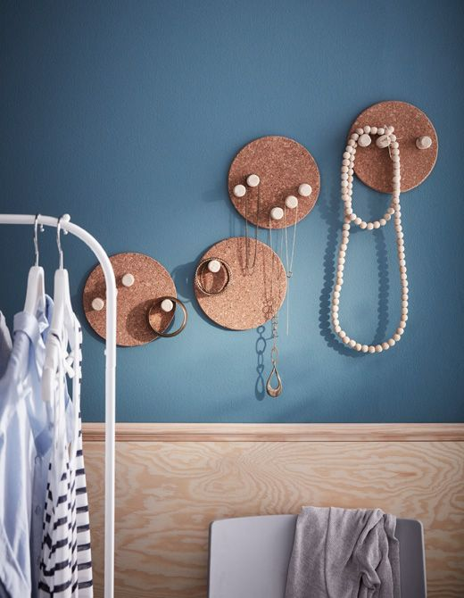 Old corks screwed into cork pot stands to make jewelry storage that hangs on a wall