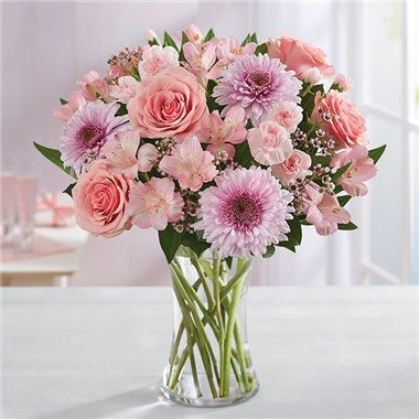 e30fe759a6ae7 All-around arrangement of pink roses, mini carnations, Peruvian lilies  (alstroemeria), and waxflower, lavender cremone, and assorted greenery  Large ...