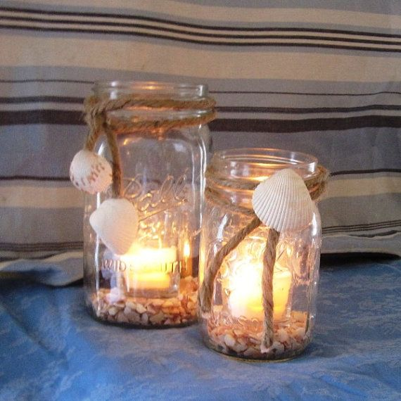 wide mouth mason jar with seashells attached on rope. crushed sea shells i bottom, small glass votice holder with candle.