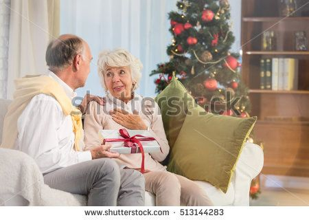 Senior husband giving christmas gift box to his wife