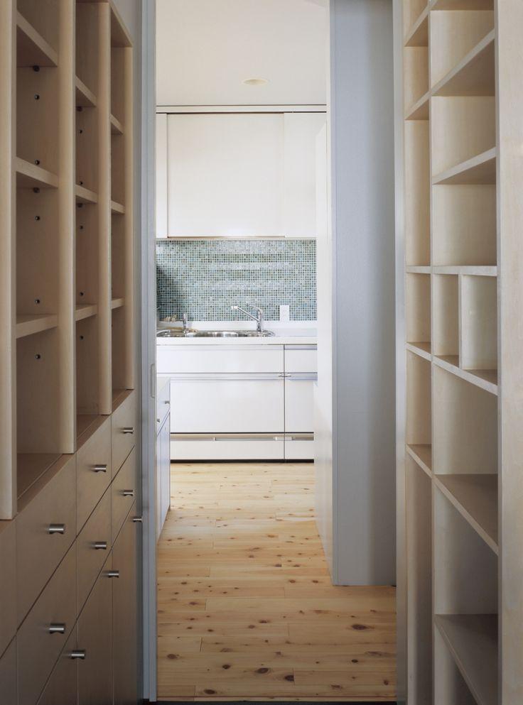 洗面側からユーティリティを通して、モザイクタイルの貼られたキッチンを見る。<br /> 左は家族の人数分のそれぞれの衣類が収まる造付棚。各個室ではなく浴室脇のこちらにまとめてあることで、洗濯後の収納の手間も減り、合理的。<br /> 右側は階段下を棚として活用。食料品のストック、瓶なども様々なサイズの棚に収まる。 専門家:山岸綾が手掛けた、ユーティリティ・キッチン(タガイ/チガイ)の詳細ページ。新築戸建、リフォーム、リノベーションの事例多数、SUVACO(スバコ)