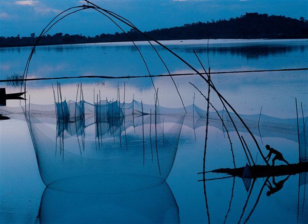 Un pescador manipula una extensa red en el río Brahmaputra  India— Anochece sobre las aguas del río Brahmaputra cerca de la ciudad de Guwahati, importante puerto fluvial del nordeste de la India. Un pescador manipula una red con ayuda de unas varas de bambú para abastecer a su comunidad.