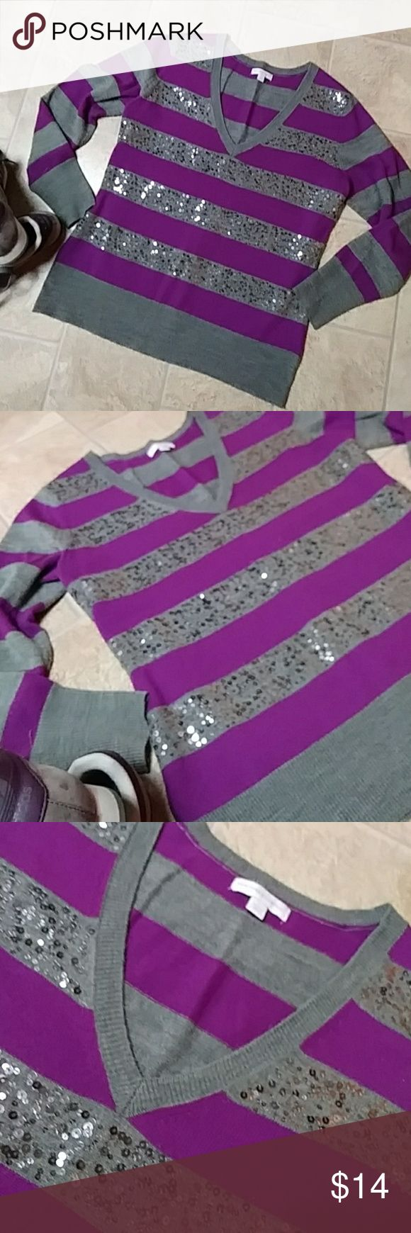 """🆕💜New York & Company v-neck sweater Pre-loved with lots of sparkle left. All sequin still attached. Gray with  nice bright purple stripes and silver sequins throughout front. Long sleeve and v-neck. Size large. Looks great on. I wore it with matching adidas and jeans with purple cami. Dress up or casual with some added bling;))  Flat chest measures approx 21""""  Under armpit to bottom measures approx 18"""" New York & Company Sweaters V-Necks"""