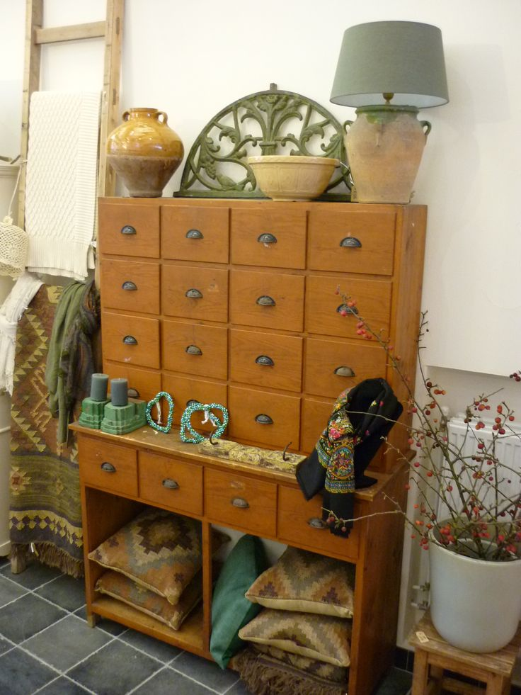 Interieur in okergeel en groen; oude winkelkast, kelimkleed en -kussens, oude kruik.