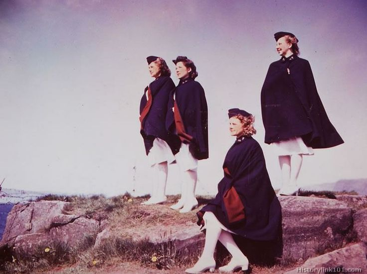 Four nurses looking out to sea. Laugarness, Iceland - June 1942. They are wearing white hospital uniforms with dark blue capes and garrison caps with maroon piping ~