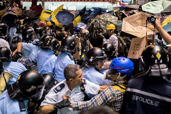 Umbrella Revolution Hong Kong, Police officers beat back pro-democracy protesters in the Mongkok district of Hong Kong on November 25, 2014. Hong Kong authorities tore down barricades at a protest site in Mongkok, the scene of some of the more violent clashes to take place during nearly two months of pro-democracy sit-ins. AFP PHOTO / ALEX OGLE (Photo credit should read Alex Ogle/AFP/Getty Images)