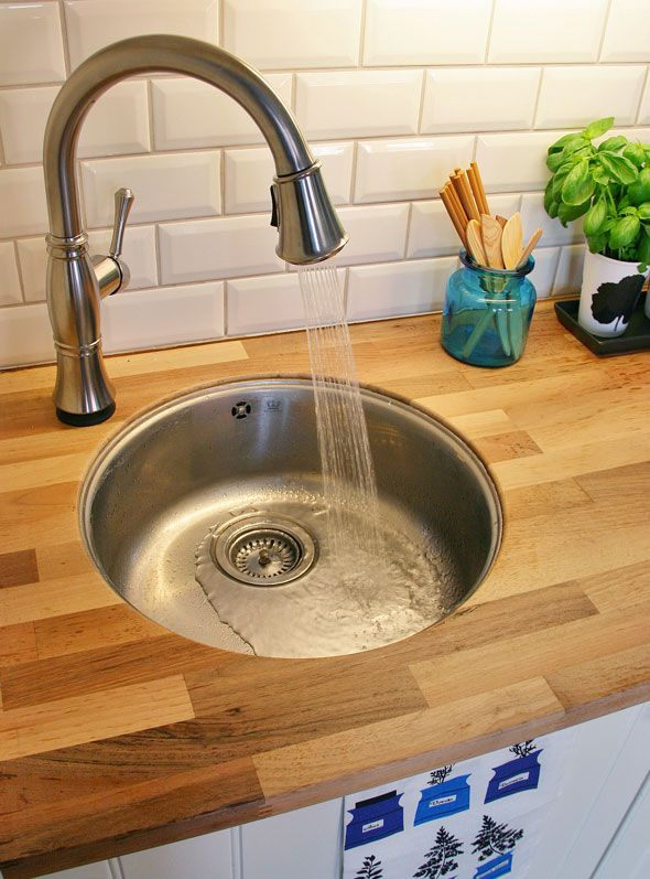 Scandinavian-style kitchen makeover featuring the Cassidy pull-down kitchen faucet with Touch2O technology by Delta Faucet.