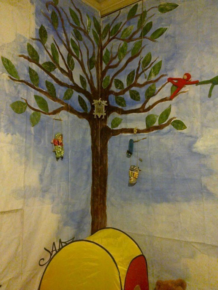 """Escenografía de pieza infantil pintada por el revés de pendones publicitarios, incorporando elementos como el cucú y algunos muñecos para darle más volumen y """"cuento""""."""