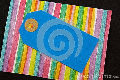 A close up of a cardboard blank label on a colourful striped background.