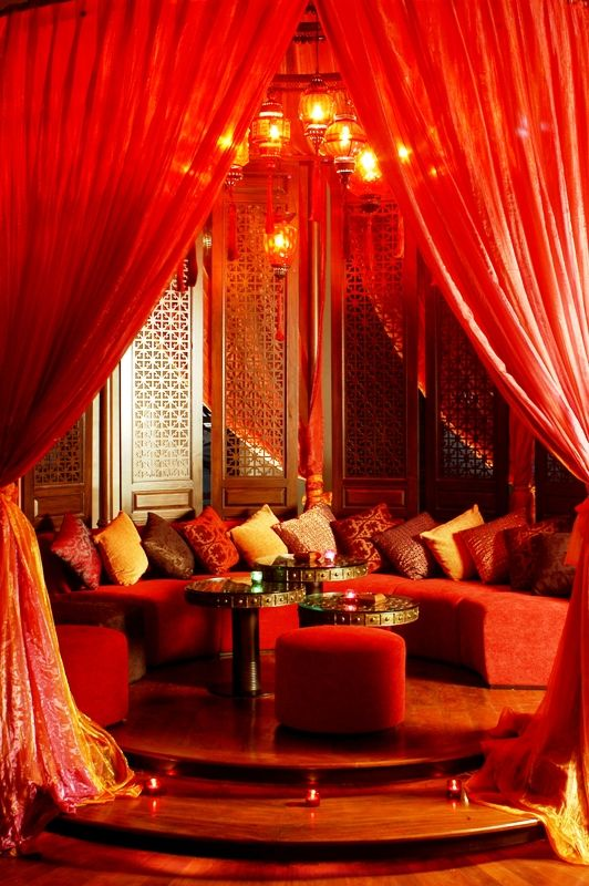 Bohemian opium den. Vibrant reds & golds with dramatic curtains.