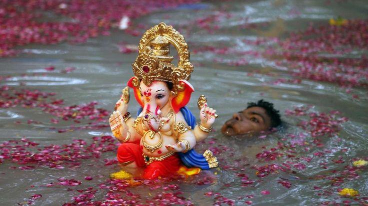 DIOSES. Un devoto hindú lleva una imagen del Dios Ganesha, que tiene cuerpo de humano y cabeza de elefante, para la inmersión en el agua, festival de Ganesh en Mumbai, India. (AP)