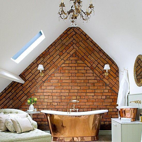 Creative bathroom under roof: Brick assymetric wall, antique bathtube and elegant chandelier.
