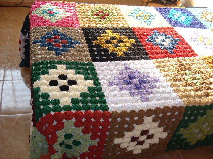 Traditional design quilt made with suffolk puffs or yo-yos.