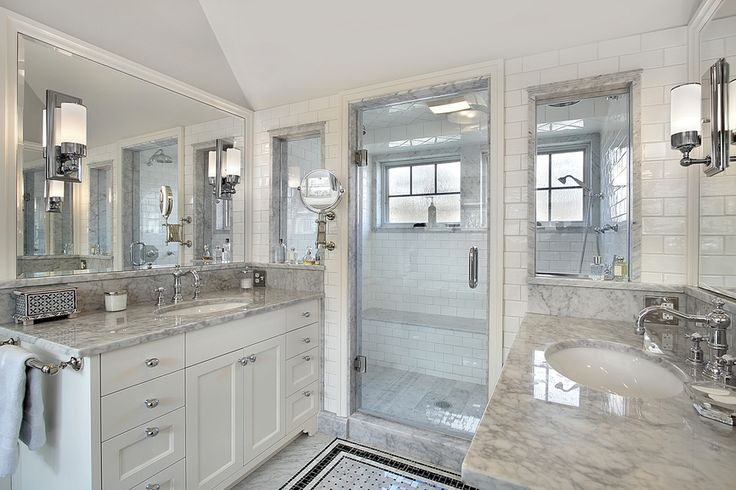 White bathroom with two vanities and separate shower room. Love the mirrors with the lights in them!