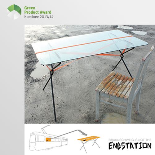 5th place Newcomers Green Product Award 2013/14, category furniture: The design of the desk ENDSTATION is based on the underlying idea to re-utilise tram windows. Due to the scratches and dents on the windows, each table tells its own story and is unique. The strap is used as a central design element to hold the plate and legs together and adjust the slight curvature of the plate at the same time.