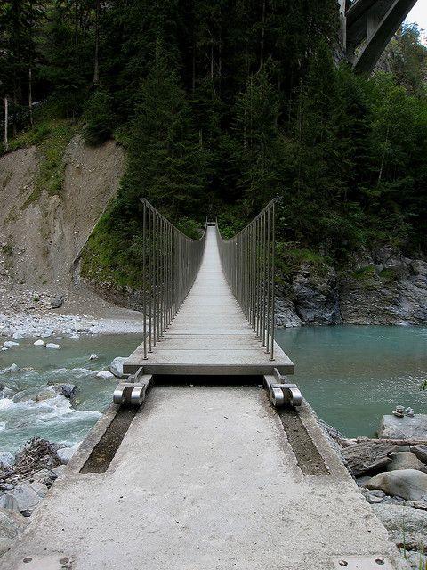 A minimalist pedestrian bridge in Graubunden Switzerland, consisting of tensile steel and stone slab decking.