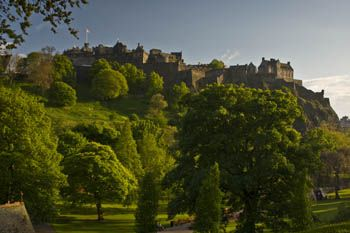Historic Edinburgh Castle, dating back to the 12th Century, seen through the trees of a local park.  Edinburgh Castle is Scotland's most popular tourist attraction, pulling in over 1.2 million visitors (in 2011), it also plays host to the Edinburgh Military Tattoo, which takes places during August's Edinburgh International Festival.