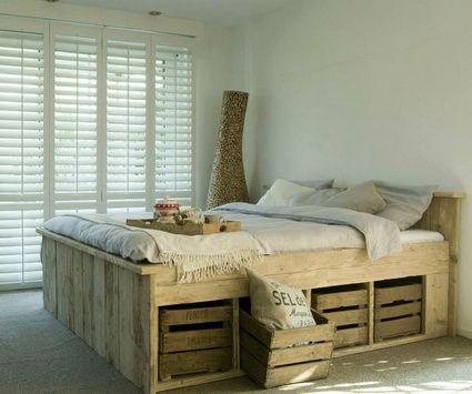 Camas hechas con palets de madera y cajones de manzana para guardado