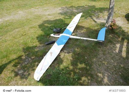 Ein ferngesteuertes Segelflugzeug steht auf dem Rasen und ist bereit zum Einsatz.