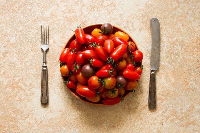 ripe cherry tomatoes on a yellow bac by Naltik on Creative Market