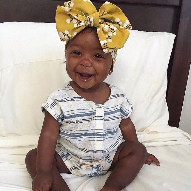 Beautiful baby girl with yellow bow headscarf.