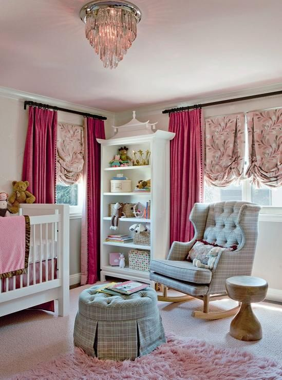 Pink and gray nursery features a pale pink ceiling accented with a crystal flush mount light illuminating a white crib dressed in pink bedding facing a white pagoda bookcase flanked by windows dressed in hot pink pom pom curtains layered over pink ruched shades.