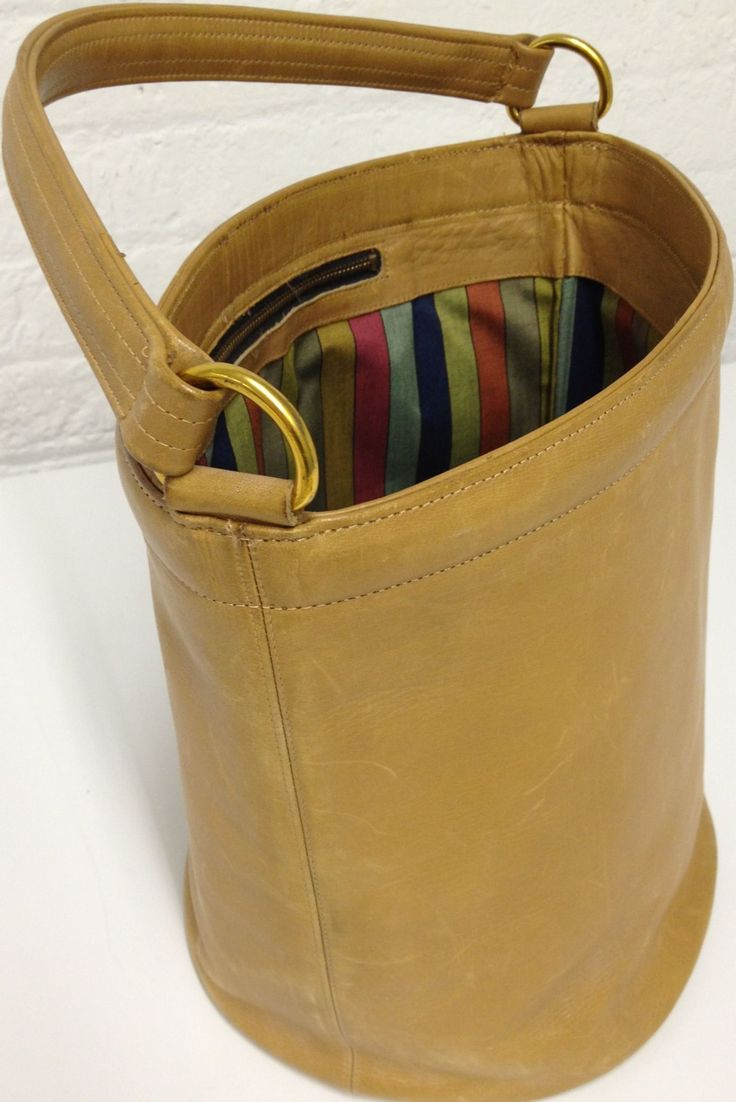 A 1968 Coach Bucket Bag with Legacy Stripe lining in Camel.