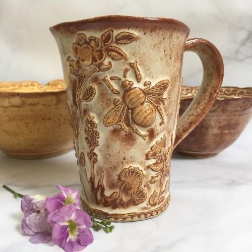 This mug has a big bee in a garden full of lavender, Queen Anne's lace, wild rose, and lily of the valley blossoms. Two of these mugs will be available in today's 11:00 AM EST Shop Update at QueenBeePottery.com  shop link in profile#bee #bees...