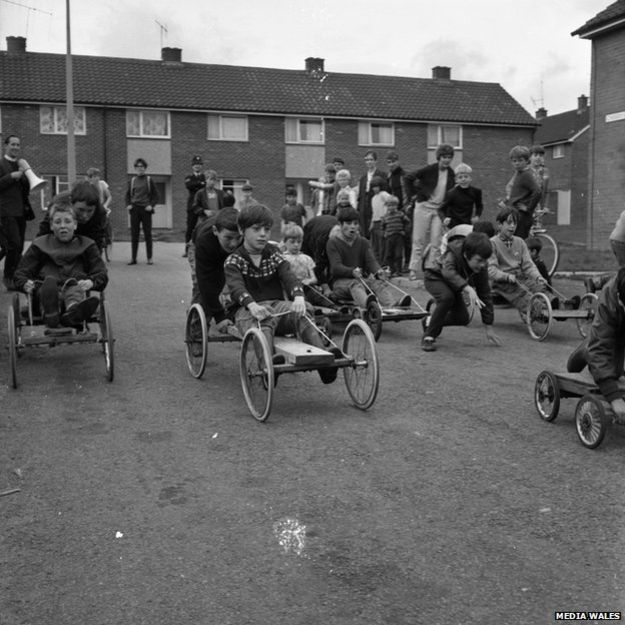 "1969, A Gambo race! - Merthyr Tydfil, South Wales, UK - ""All the go karts are home made, made out of scaffolding planks, wheels from a pram, bit of chord for driving and feet for brakes! You put your feet on the wheels and hope they slow down. They were good days where we just made our own enjoyment."""